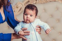 De oude baby van drie maanden in de handen van moederclose-up Stock Foto's