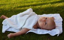 De oude baby van twee maand ligt op het gras Stock Afbeelding