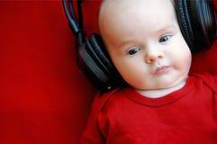 De oude baby van twee maand met oortelefoons Royalty-vrije Stock Afbeeldingen