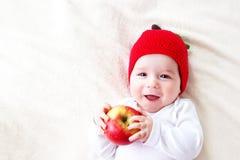 De oude baby van zeven maanden met appelen Stock Afbeelding