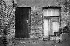 De oude baksteenbouw met houten deur en venster royalty-vrije stock afbeeldingen