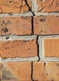 De oude bakstenen muur van een rode baksteen met barsten, bakstenen zette op cement stock foto's