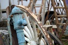 De oude blauwe antieke pomp van het ijzerwater en grote witte cartwheel met uitstekende houten ladders op achtergrond Royalty-vrije Stock Afbeeldingen