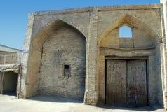 De oude bogen van Boukhara van witte baksteen met houten poort Royalty-vrije Stock Foto's