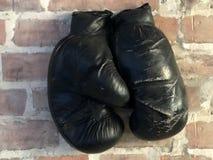 De oude bokshandschoenen hangen op spijker stock foto's