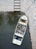De oude boot voor het verzamelen van binnenlands afval die in het water drijven is dichtbij de waterkant de moeite waard Stock Foto