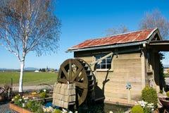 De oude cabine van het Land met decoratief waterwiel Stock Foto