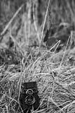 De oude camera ligt op het droge gras Royalty-vrije Stock Afbeeldingen