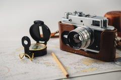 De oude camera van de filmfoto, magnetisch kompas en potlood die op kaart liggen stock afbeeldingen