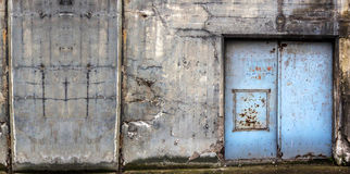 De oude concrete bouw met blauwe deuren Stock Afbeeldingen