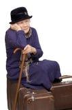 De oude dame zit op een koffer Stock Afbeeldingen