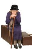 De oude dame zit op een koffer Stock Foto