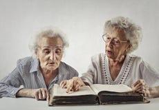 De oude dames proberen samen te lezen stock foto