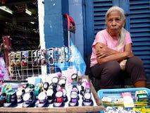 De oude damestraatventer verkoopt horloges en eyewear royalty-vrije stock afbeeldingen
