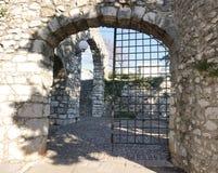 De oude oude deuropening van de kasteelsteen met ijzerpoort stock foto's