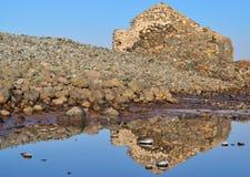De oude die steenbouw in het zoutwater wordt weerspiegeld stock foto's