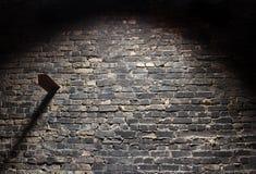 De oude donkere achtergrond van de grungebakstenen muur met licht Stock Foto's