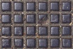 De oude donkere textuur van het metaalmangat met vierkant patroon, macro, selectieve nadruk als achtergrond Stock Foto
