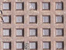 De oude donkere textuur van het metaalmangat met vierkant patroon, macro, selectieve nadruk als achtergrond Royalty-vrije Stock Afbeelding