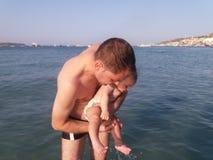 De oude eerste keer die van vier maanden van de babyjongen in het overzees zwemmen Stock Afbeeldingen