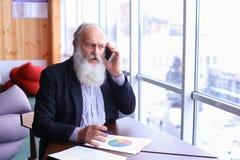 De oude ervaren mens van de bankwezenrekening geeft advies door nieuwe sma te gebruiken Royalty-vrije Stock Foto
