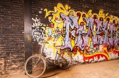 De oude fiets leunt op de muur van de kunstgraffiti, 798 straat, Peking op 25 Mei 2013 Stock Foto's