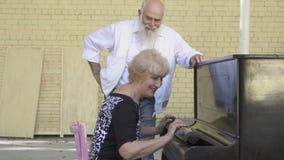 De oude gebaarde mens biedt zijn vrouw aan om piano te spelen stock footage