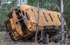 De oude gele roestbus legt verlaten in het bos van de de Uitsluitingsstreek van Tchernobyl royalty-vrije stock fotografie