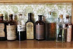 De oude geneeskundeflessen op de plank bij een ouderwetse drug winkelen in het historische Sherbrooke-Dorp in Nova Scotia Stock Afbeelding