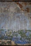 De oude gepleisterde bakstenen muur met de resten van schil schildert verschillende lagen en kleuren Stock Afbeelding