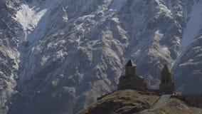 De oude Gergeti-dichtbijgelegen Drievuldigheidskerk zet Kazbek, de bergen van de Kaukasus op stock footage