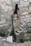De oude geroeste pomp van het handwater op steenrichel stock foto's