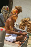 De oude geschilderde mens vraagt liefdadigheid in de tempels Stock Afbeeldingen