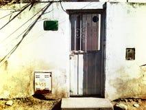 De oude grijze deur van het bladmetaal in een versleten muur royalty-vrije stock afbeeldingen