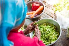 De oude groente van het vrouwenknipsel in een dorp in Thailand royalty-vrije stock fotografie