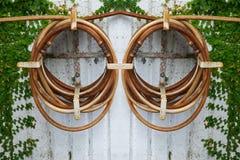 De oude het water geven slang hangt op de concrete muur Stock Foto