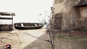 De oude houten boot is op de kust van een bergrivier lengte Gebroken Oude vissenboot op een zandkustlijn van het overzees dichtbi stock footage