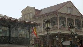 De oude houten bouw met vlaggen van Spanje en Georgië op regenachtige dag, diplomatie stock footage