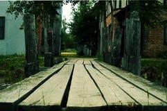 De oude houten brug door de rivier stock afbeelding