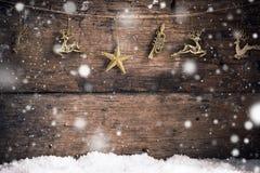 De oude houten textuur gouden ster, het gouden rendier en de decoratie met sneeuw schilferen Kerstmisachtergrond af stock afbeelding