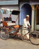 De oude Indische mensenriksja rolt zijn fiets op straat Royalty-vrije Stock Foto's