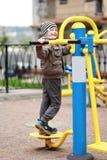De oude jongen die van vijf jaar in de straat, in de openluchtgymnastiek op de speelplaats uitwerken Royalty-vrije Stock Foto's