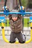De oude jongen die van vijf jaar in de straat, in de openluchtgymnastiek op de speelplaats uitwerken Royalty-vrije Stock Afbeelding