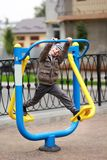De oude jongen die van vijf jaar in de straat, in de openluchtgymnastiek op de speelplaats uitwerken Royalty-vrije Stock Afbeeldingen