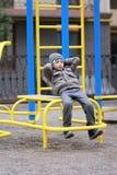 De oude jongen die van vijf jaar in de straat, in de openluchtgymnastiek in de werf op de speelplaats uitwerken Royalty-vrije Stock Fotografie