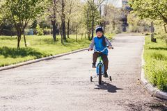 De oude jongen van vijf jaar in een blauw vest die een fiets in een de lentepark berijden royalty-vrije stock foto's