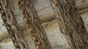 De oude kettingen hangen op een houten logboekmuur stock foto's