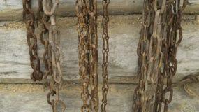 De oude kettingen hangen op een houten logboekmuur royalty-vrije stock foto's