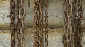 De oude kettingen hangen op een houten logboekmuur stock fotografie