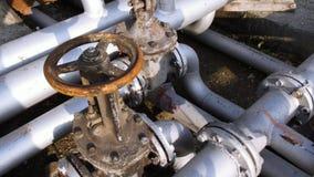 De oude kleppen van de brandstofoverdracht op een gebouw in de industriezone voorraad Oud de brandstofklep bij het tanklandbouwbe stock footage